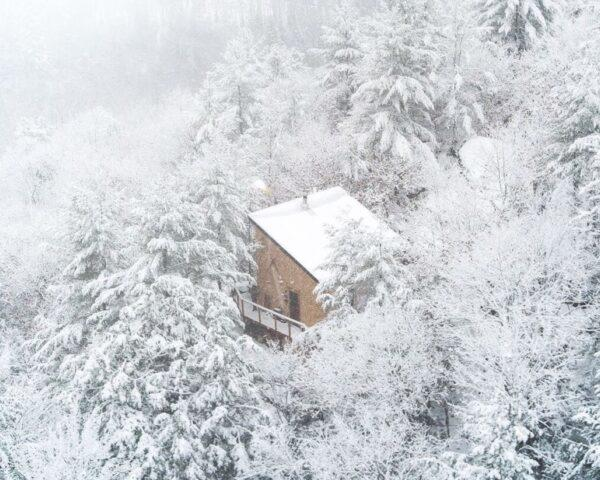 A small cabin in the middle of a snowy forest.