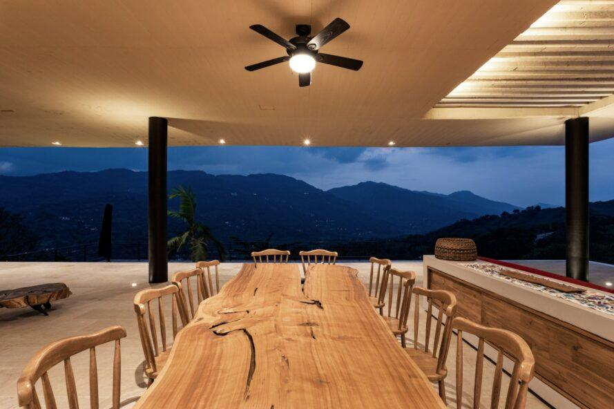 long wood dining table facing open wall with mountainous views