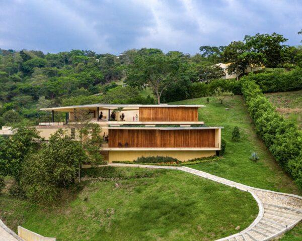 white and teak home built on a slope