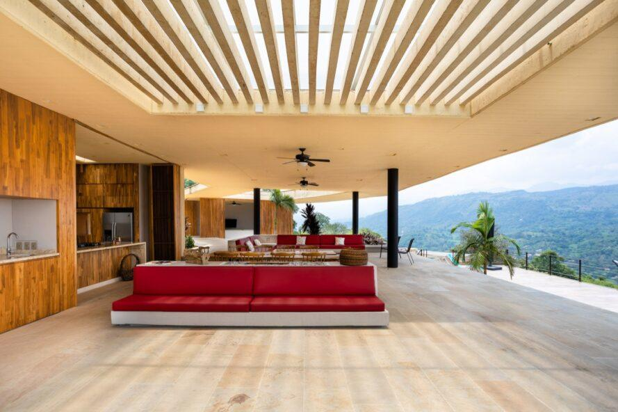 red sofa in wood-lined living room with one wall open to the outdoors