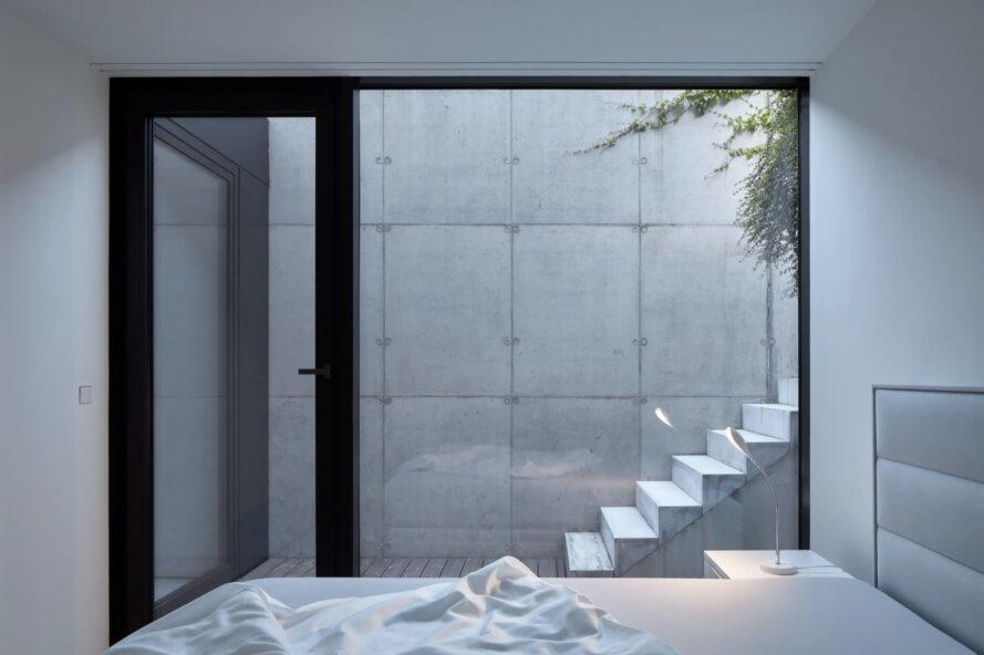 white bedroom with glass wall revealing set of outdoor steps