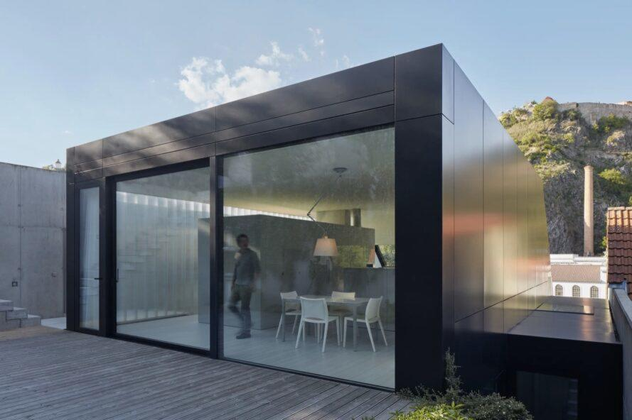 black metal home with sliding glass door leading to wood patio
