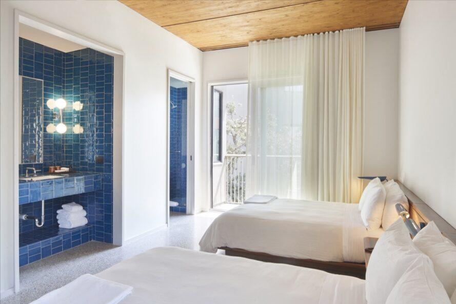 white hotel room with two beds