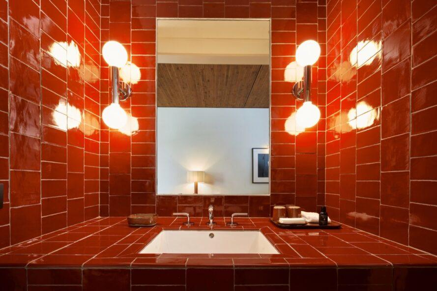 bathroom with large mirror and red tiles