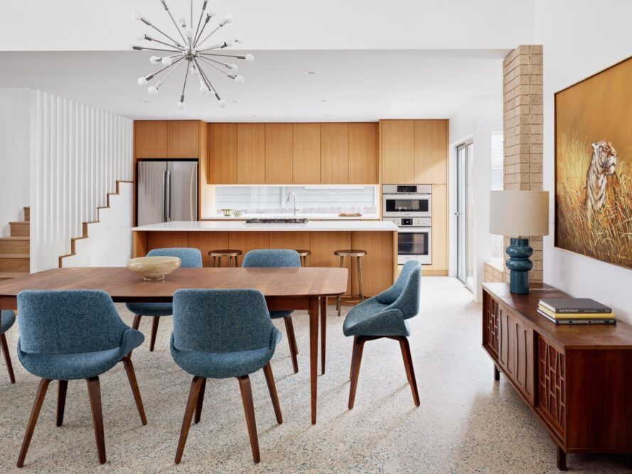 wood dining table with blue chairs near a kitchen with wood cabinets