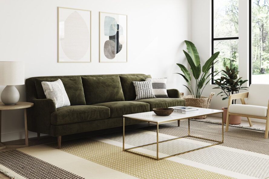 A green sofa and minimalist coffee table in a living room.