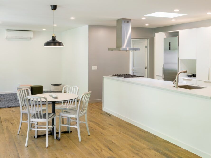 small round dining table near large white kitchen