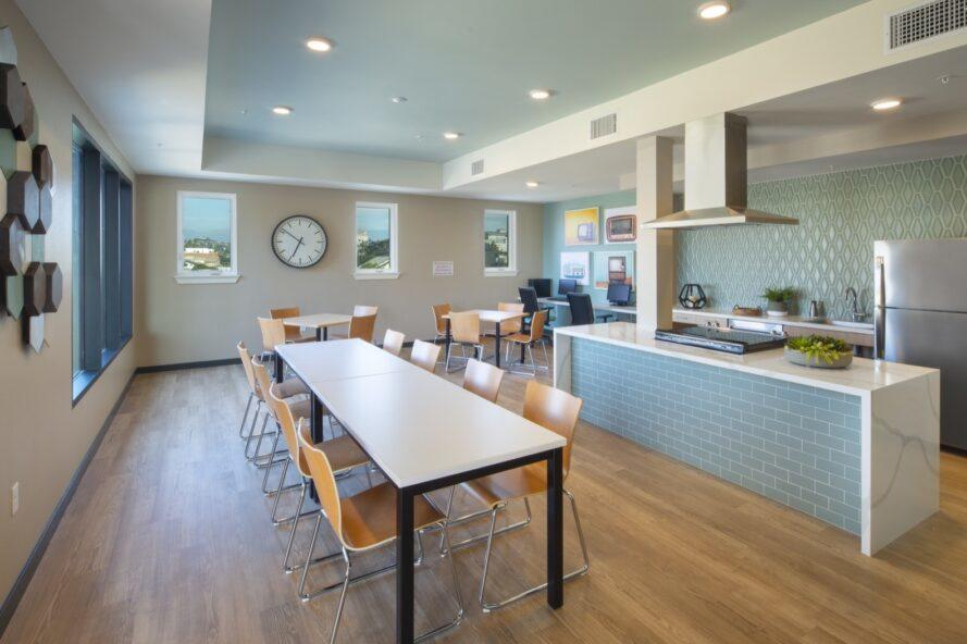 communal kitchen with large stove and a long wood dining table