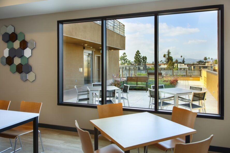 wood dining tables near wall with large windows overlooking an outdoor patio
