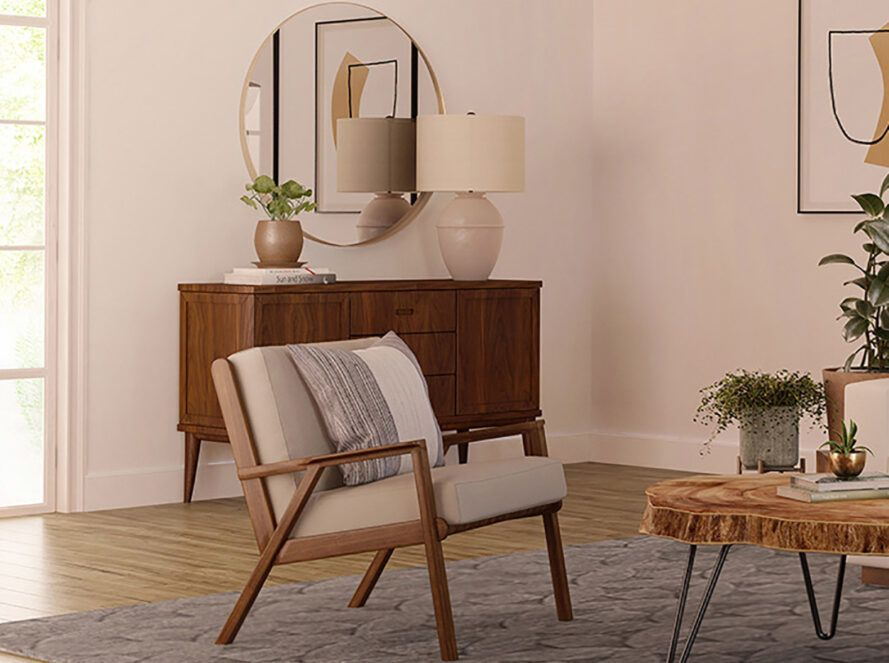 A wood frame chair with off-white cushions in a living room.