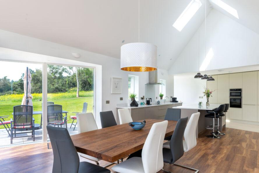 long wood dining table with gray, white and black chairs across from glass wall
