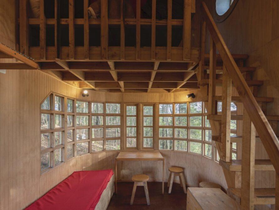 wood cabin with small red bench, wood table and stools and a loft above