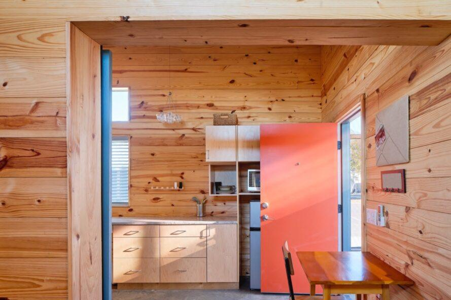 wood-lined interior with orange front door and wood kitchen cabinets