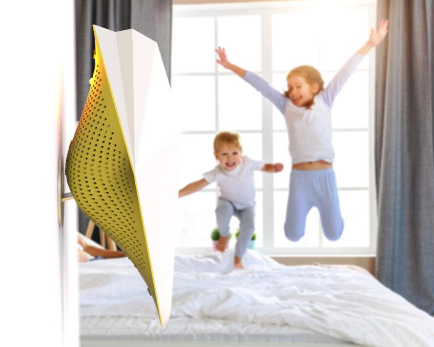 yellow bird-shaped air monitor on wall with kids jumping on bed in background