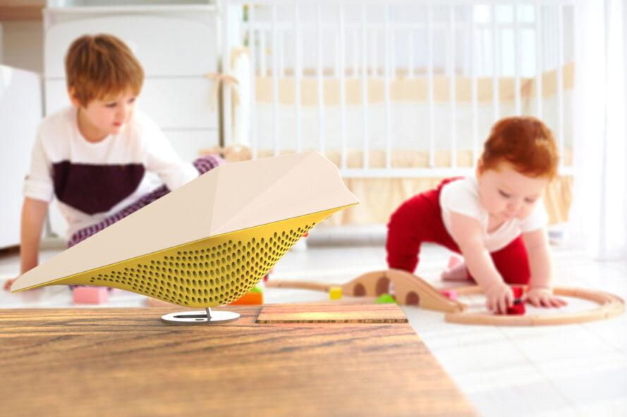 yellow bird-shaped air monitor on table with kids playing with blocks in the background