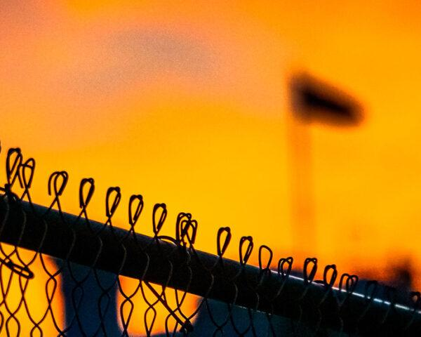 A close-up of a border fence with a flag in the background.