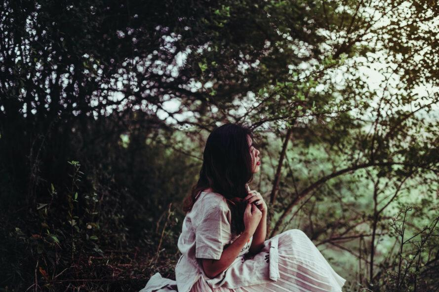 person in embroidered cotton dress sitting in a forest