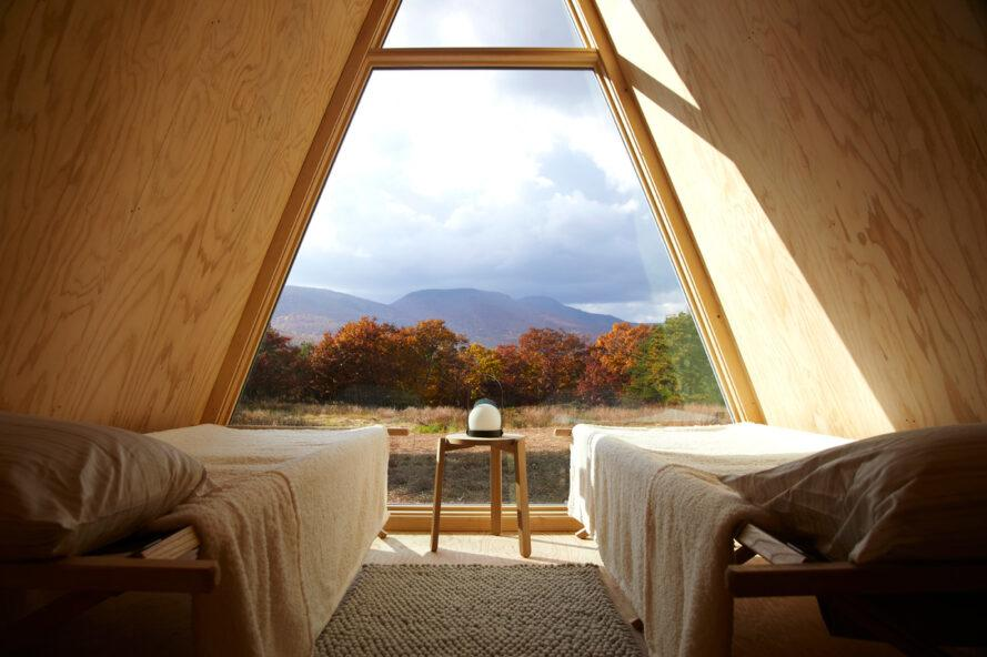 two beds facing wall of glass inside a-frame wood cabin