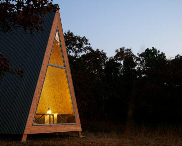 light glowing within a-frame wood cabin at dusk