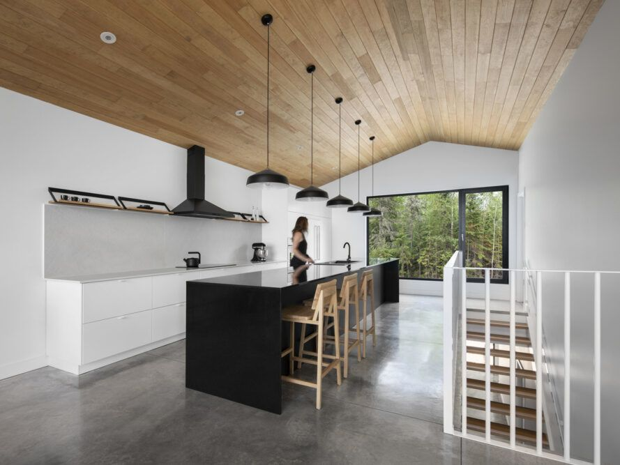 white room with wood ceiling and black island in the kitchen