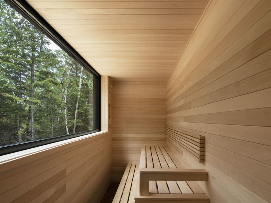 wood-lined sauna with large window overlooking a forest