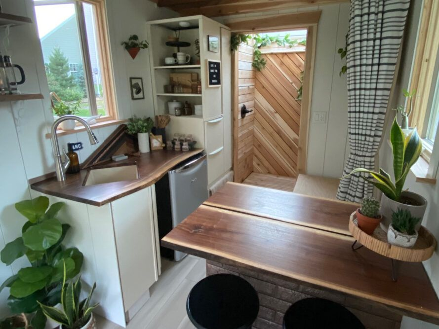 tiny kitchen with wood counters and white cabinets