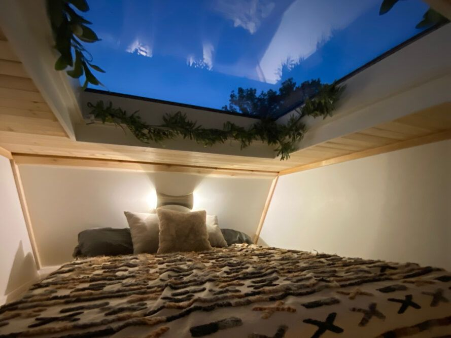 large lofted bed under a skylight