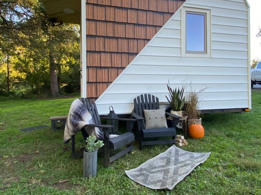 two black patio chairs outside a white and wood tiny home