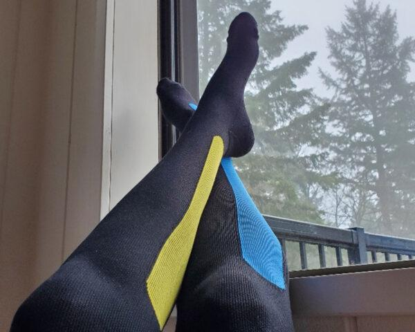 person wearing compression socks with feet resting against window