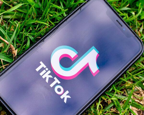 tiktok on iPhone in the grass