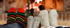 people in cozy socks with feet near fireplace