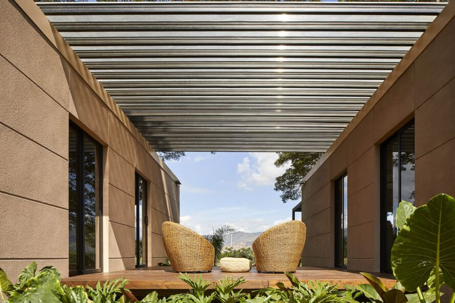An outdoor sitting area with chairs covered by a pergola.