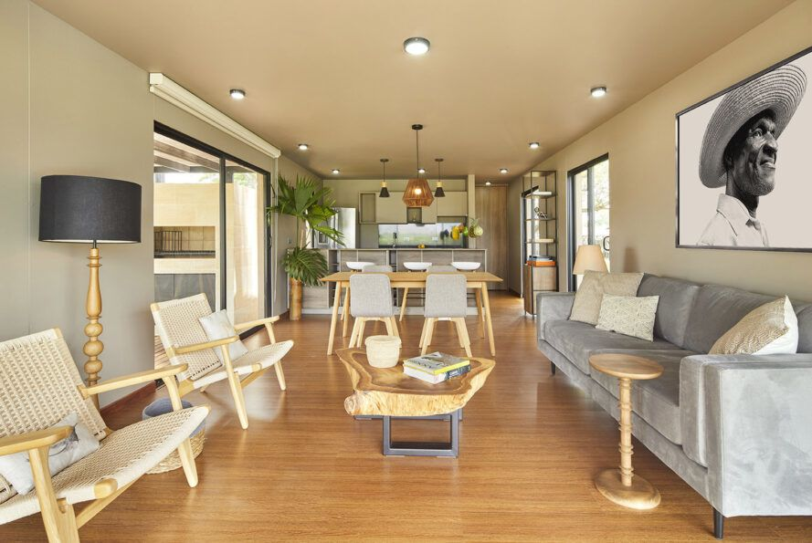 A living room with wood chairs and coffee table. A light blue/gray sofa sits on the right side of the room.