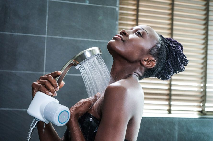 A person spraying water on their body in the shower. The showerhead has a white Shower Power device on it.