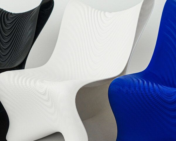 Three 3D-printed chairs. From left to right, the chairs are black, white and blue.