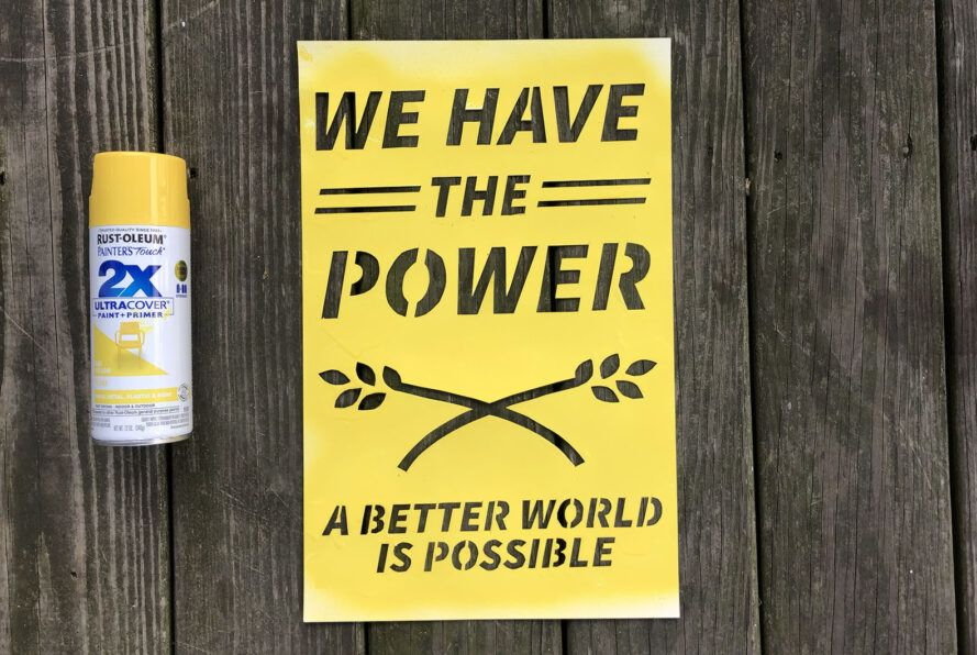 """A yellow spray-painted sign saying """"We have the power. A better world is possible."""""""
