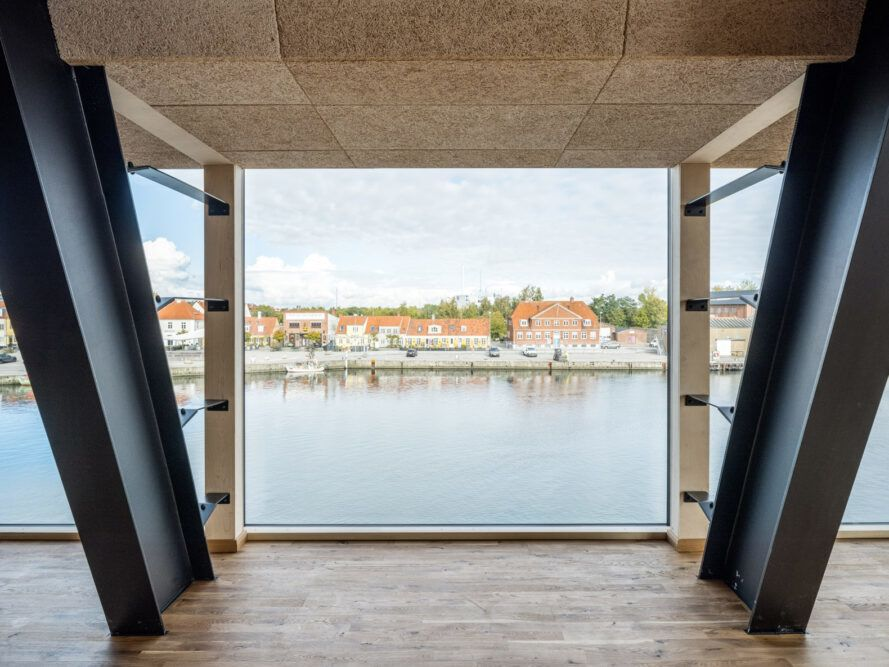 large window framing views of a harbor