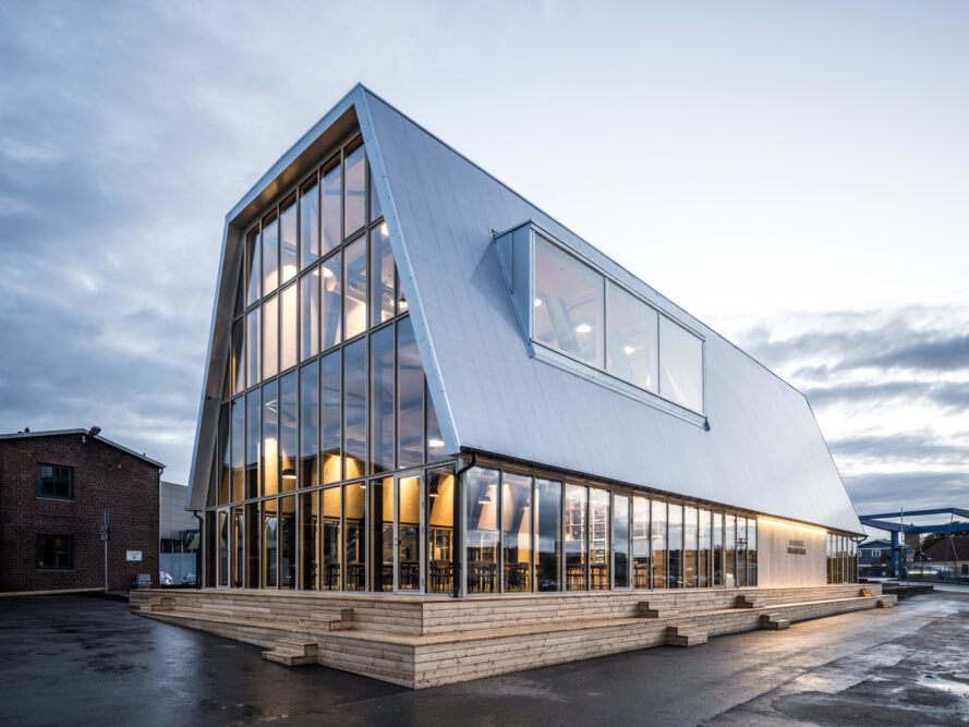 glass building with angled metal roof