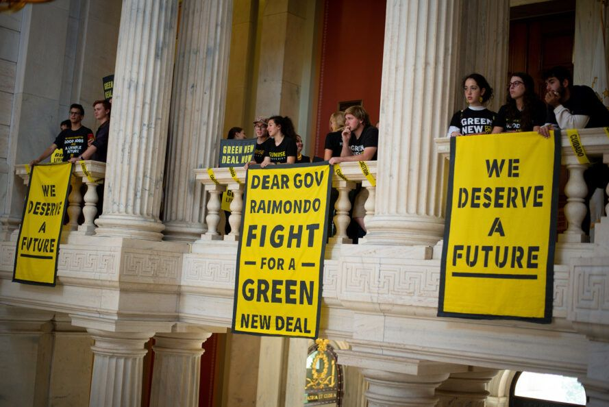 A group of Sunrise Movement activists holding a protest in a capitol building.