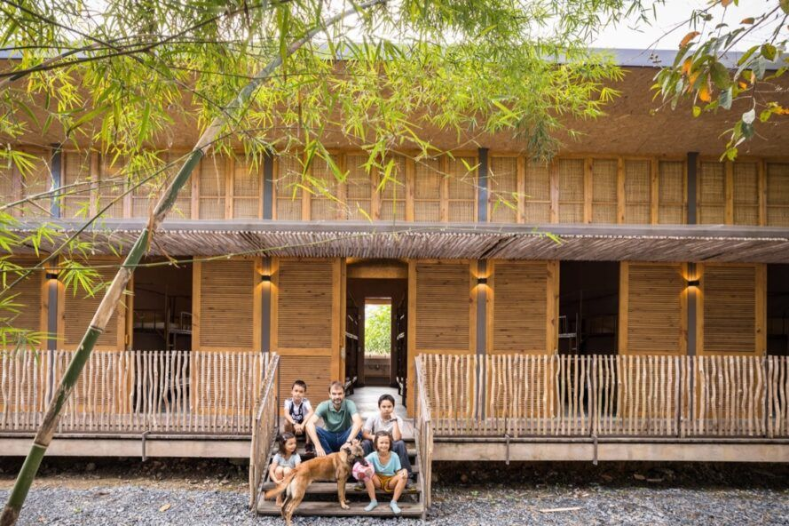 A two-story building with natural materials of bamboo and rice husk, with a family of five and a dog sitting on the front porch.