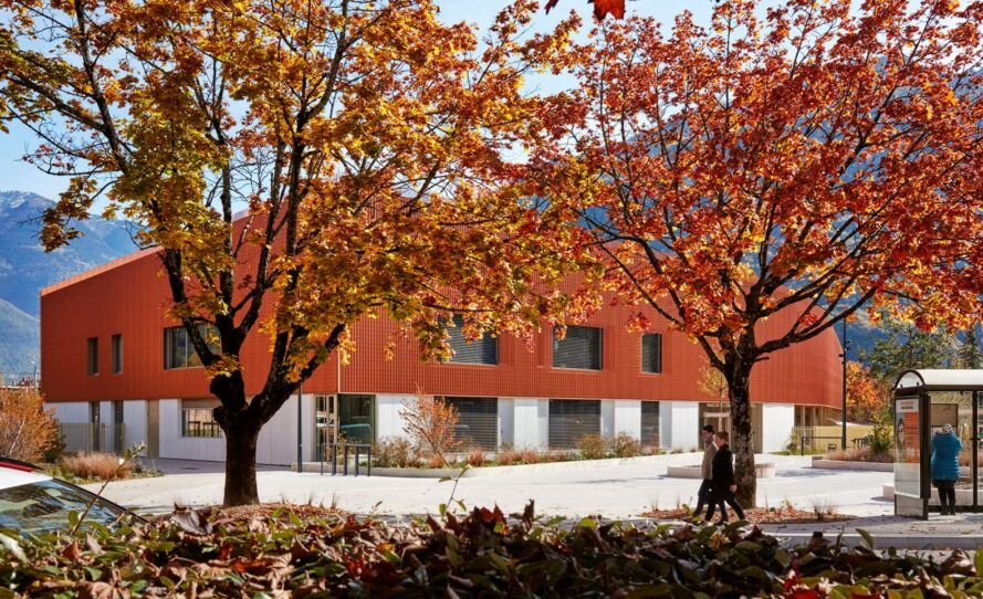 orange trees in front of bronze and concrete building