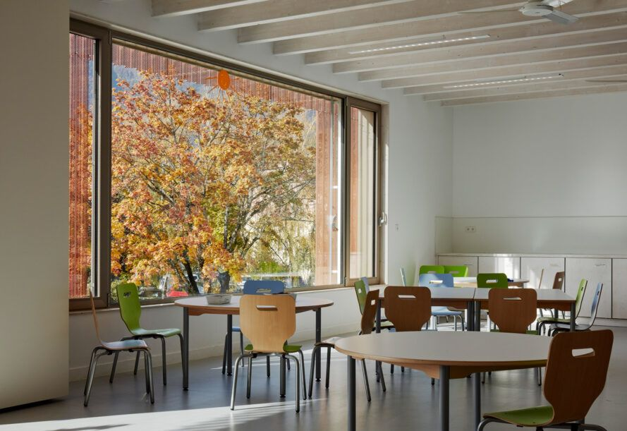round wood tables and colorful chairs next to large window