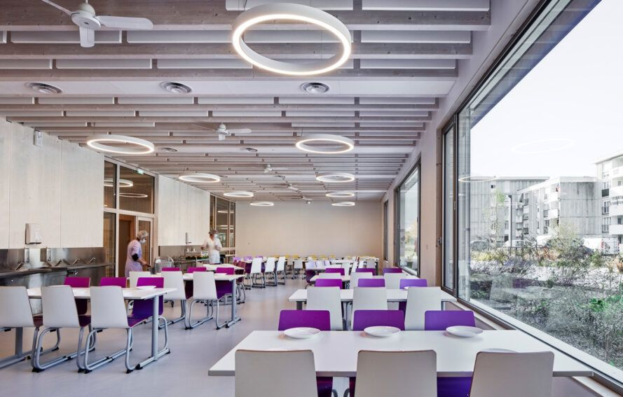 long white tables with purple chairs in room with wood ceilings and glass walls