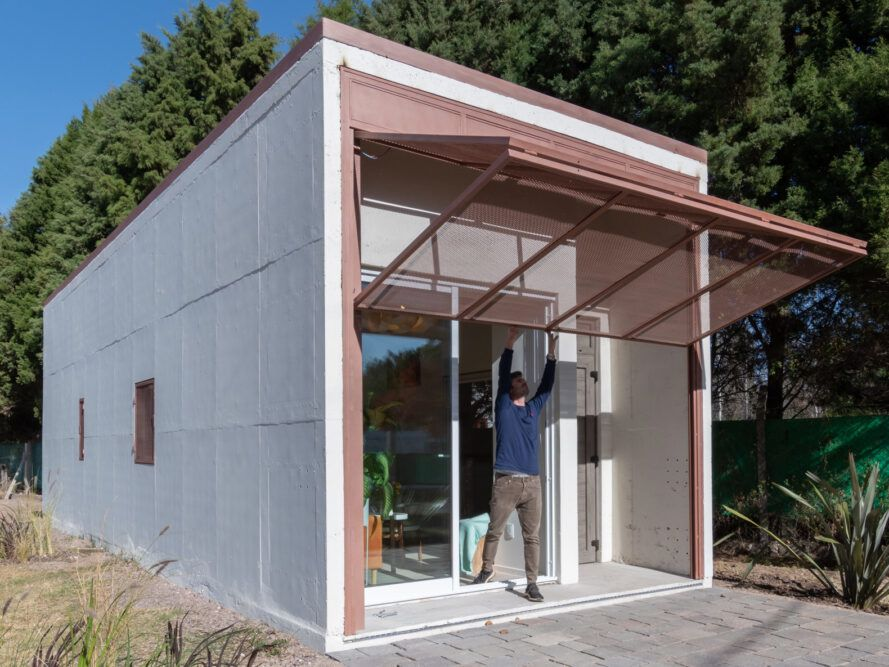 person folding up a metal screen on a concrete home