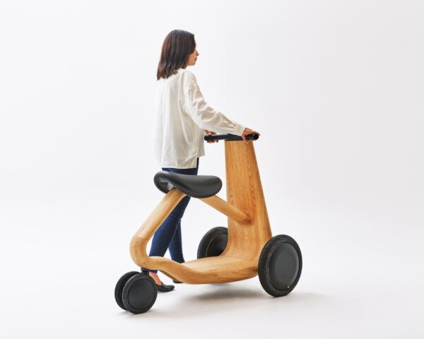 person walking and pushing wood scooter