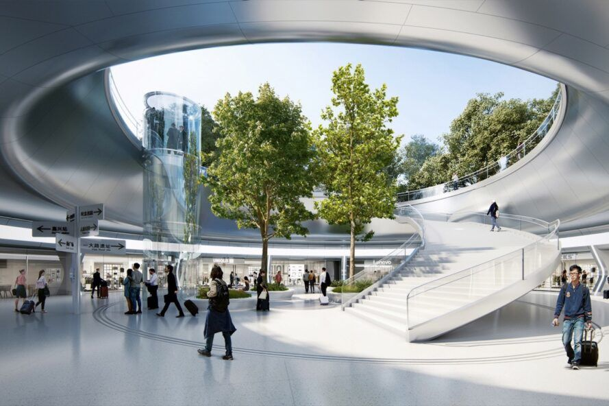 The interior of a modern, white and silver train station with two trees in the middle and a curving staircase.