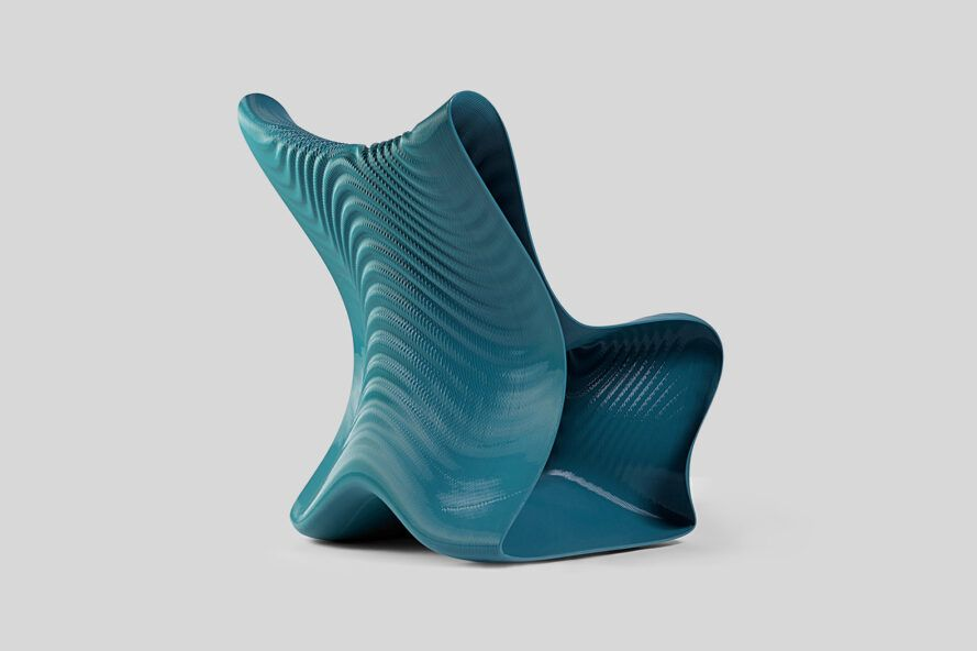 A right-back view of a dark turquoise 3D-printed chair with a wavy design and texture.