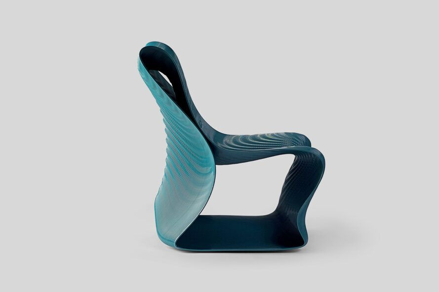 A side view of a dark turquoise 3D-printed chair with a wavy design and texture.