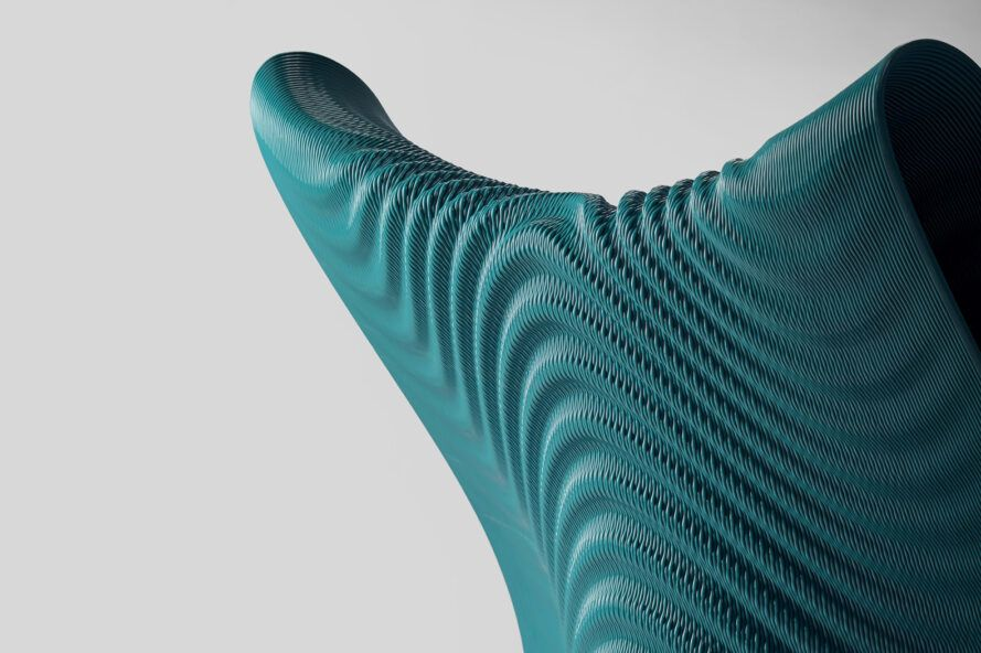 A close-up of the top of a dark turquoise 3D-printed chair with a wavy design and texture.