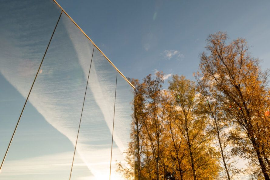 mirrored facade reflecting trees and sky